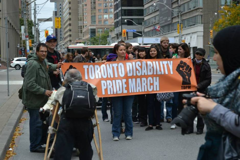 People at the Toronto Disability Pride March 2016 holding the banner